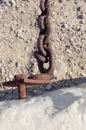 rusty chain: rusty chain on a background of sand and stones Stock Photo