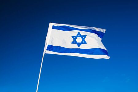 Israeli flag closeup on background blue sky