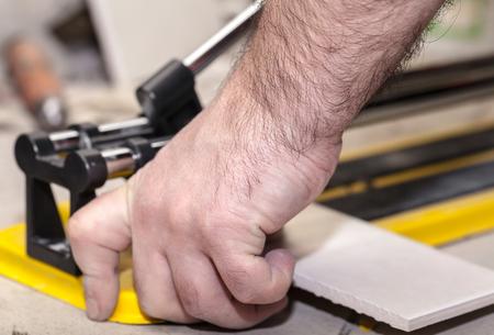 tile cutter: Worker man cuts the ceramic tile closeup