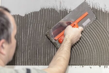 tiler: Worker tiler put cement on the wall Stock Photo