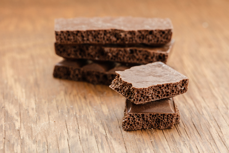 porous: part porous chocolate close-up on a wooden background