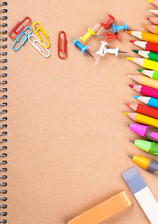 paperclips: Notebook closeup with colored pencils, erasers, paperclips and buttons