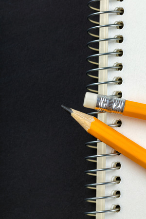 sharpened pencil and a notebook on black background Stock Photo