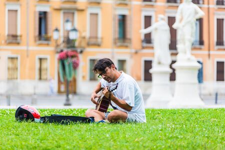 PADUA, ITALY - August 5, 2016: Piazza of Prato della Valle, Padova, Italy.A man plays the guitar.