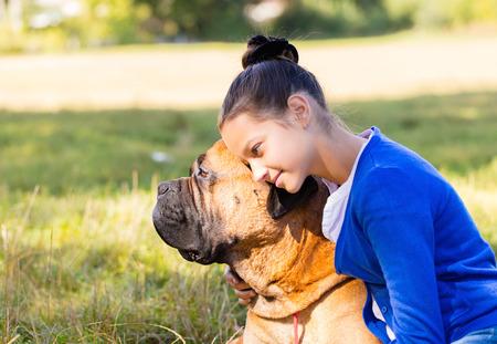teen girl with the dog Bullmastiff outdoors