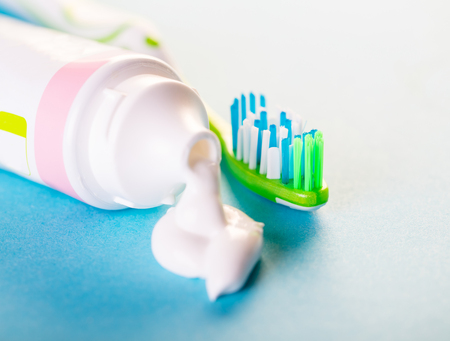 toothbrush with toothpaste close-up on blue background