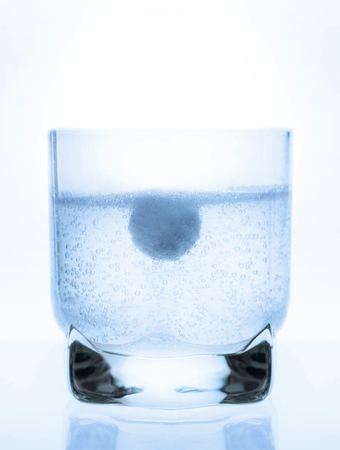 aspirin tablet in a glass of water, white background