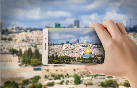 flicking: Hands with the phone close-up.Woman photographs the urban landscape on a smartphone Stock Photo