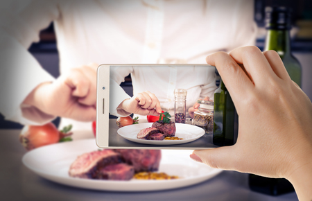 Hands with the phone close-up.Woman photographs the cooked meat to a smartphone