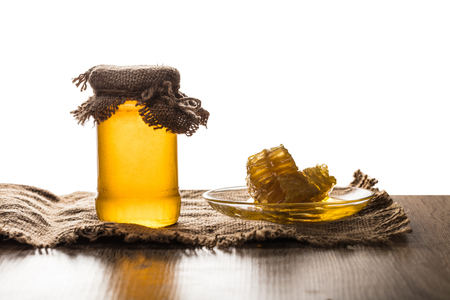 jar with honey and honeycomb on white background