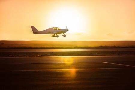 日の出の滑走路の背景に小型飛行機