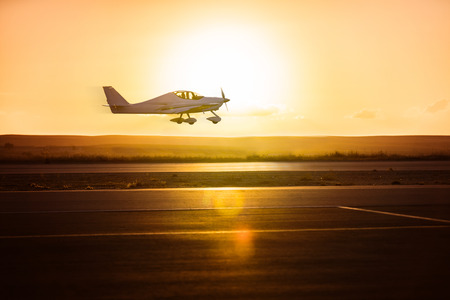 small plane on the runway background of sunrise Stock Photo