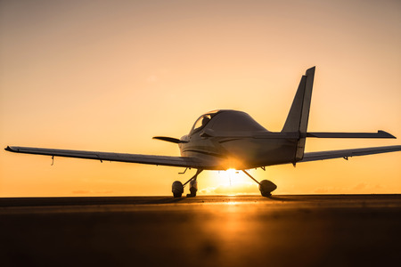 small plane on the runway at sunset background