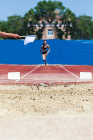 Athletic competition, athlete accelerates for long jump