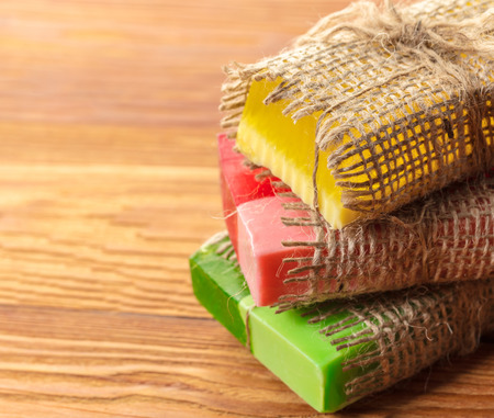 Colored handmade soap in a vintage packaging on wooden background