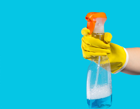 sirviente: Detergent for cleaning in a female hand on blue background Foto de archivo