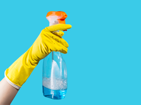 Detergent for cleaning in a female hand on blue background Stock Photo