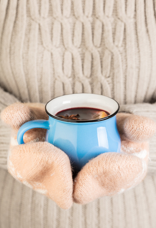 female hands in gloves holding hot mulled wine