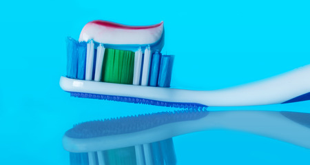 toothbrush with paste on a blue background with reflection Stock Photo