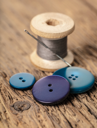 spool of threads and buttons on a wooden background Archivio Fotografico