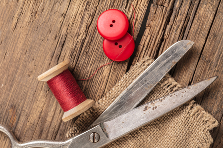 red thread with buttons and scissors, wooden background