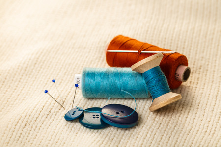 colored thread and buttons on white knitted fabric Archivio Fotografico
