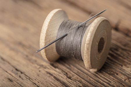 spool of thread with a needle on wooden background Фото со стока