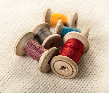 coils of colored thread on white knitted fabric