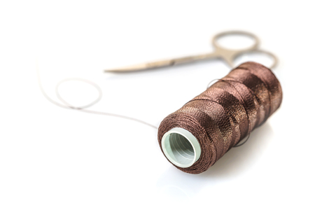 spool of brown threads on a white background