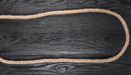 old rope closeup on black wooden background 版權商用圖片