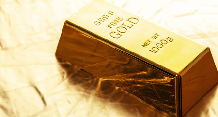 bar of gold close-up on golden background Stock Photo