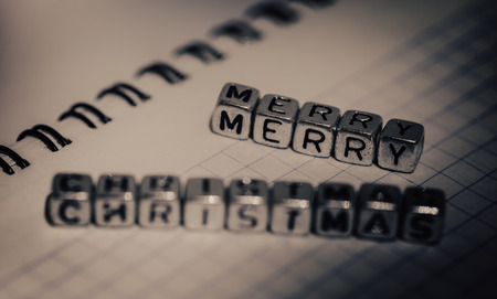 inscription Merry Christmas on background of notebook in a cage