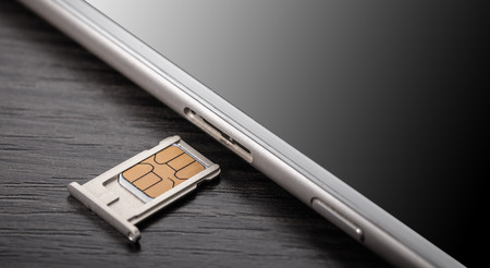 mobile phone and sim card on a wooden background 免版税图像