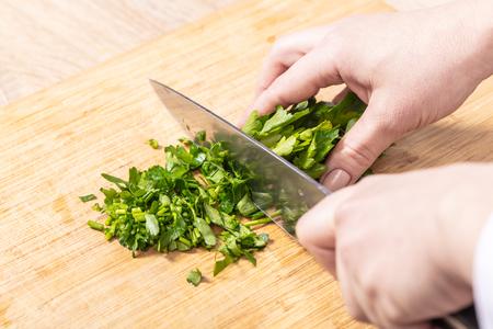 cook chopped parsley on wooden board closeup Reklamní fotografie