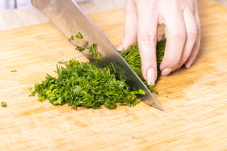 cook chopped green dill on a wooden board