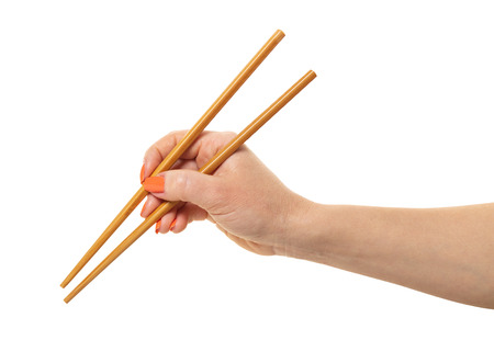 female hand with chopsticks on a white isolated background Stock Photo