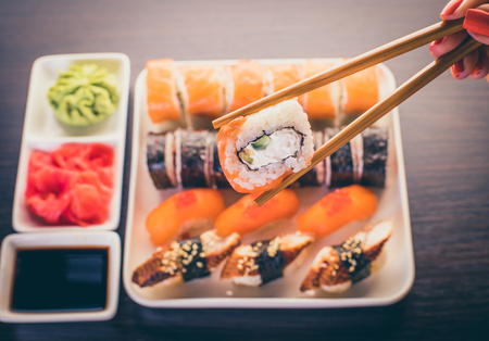 female hand takes sushi roll with salmon chopsticks