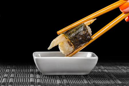 sushi immerso in salsa di soia su sfondo nero