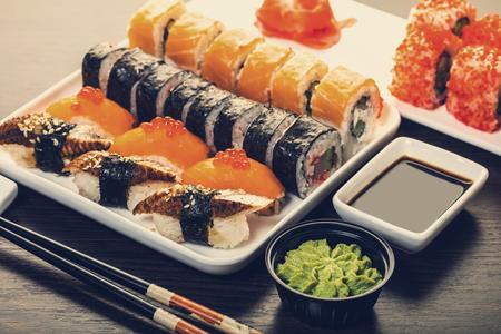 rouleau de sushi situé dans une assiette sur fond de bois Banque d'images