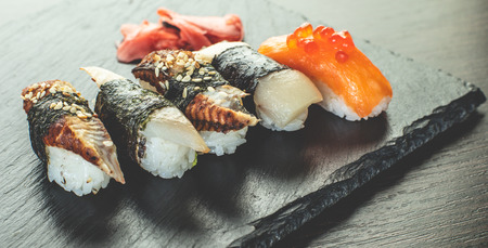 sushi set on black stone board, wooden background Stock Photo