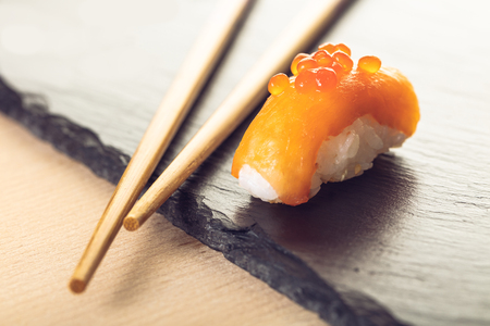 salmon sushi and chopsticks on a stone board Stock Photo