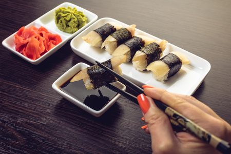 womans hand dipping sushi in soy sauce