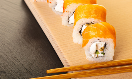 salmon sushi roll and chopsticks on wooden board Stock Photo