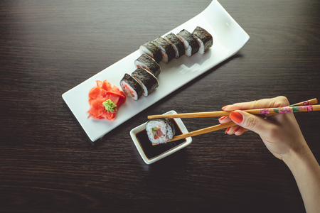 sushi roll dipped in soy sauce closeup Stock Photo