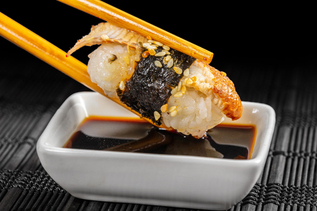 sushi dipped in soy sauce on a black background