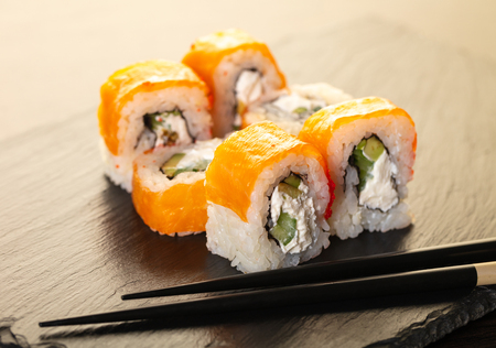 salmon sushi roll and chopsticks on stone board