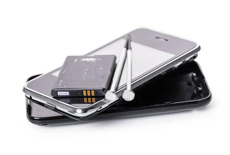 Teléfono móvil desmontado y herramientas sobre fondo blanco aislado