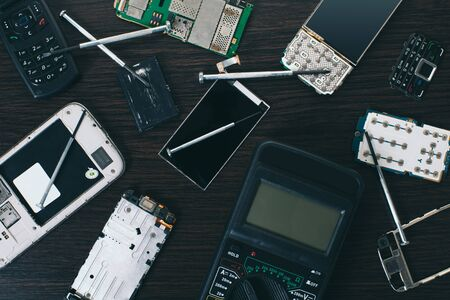 disassembled mobile phone and tools on wooden background