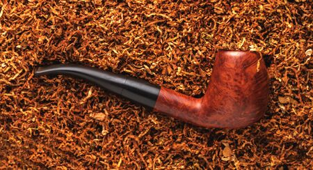 smoking pipe close-up on a background of dry tobacco 版權商用圖片
