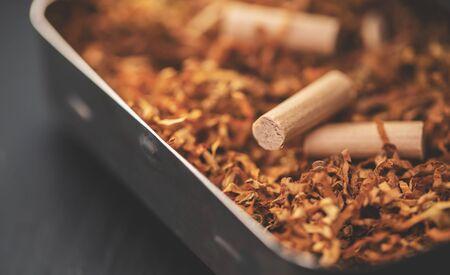 cigarette machine with tobacco on a black background